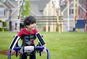 Disabled boy in walker in front of playground